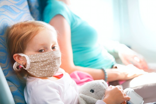 girl on airplane with face mask