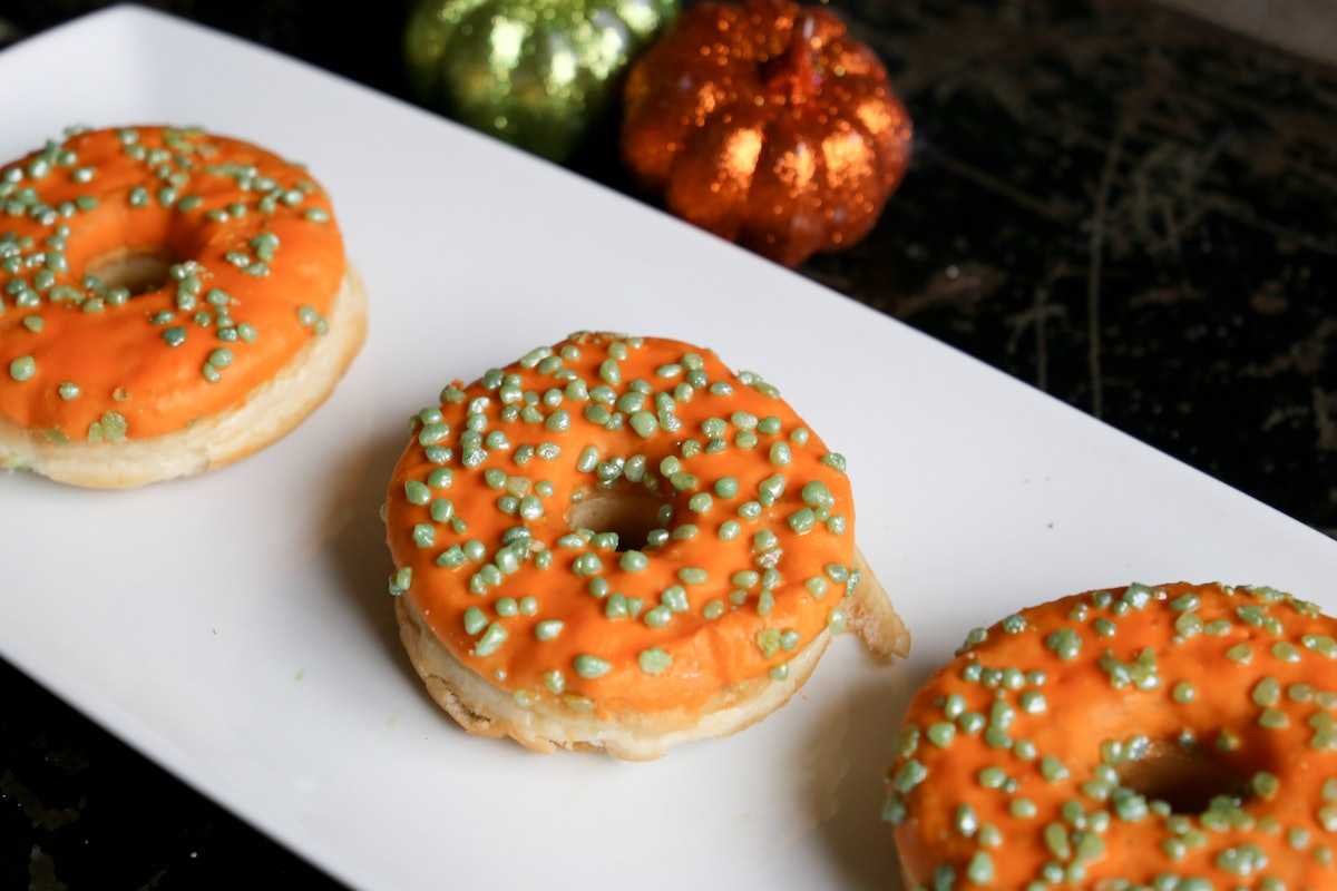A tray of orange doughnuts sits on the table with mini pumpkins.
