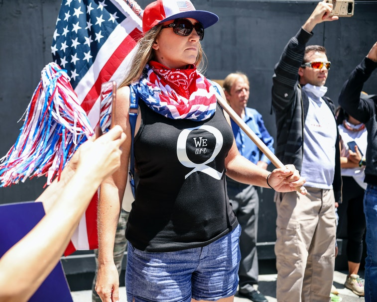A QAnon protester in an American flag can be seen at a rally.