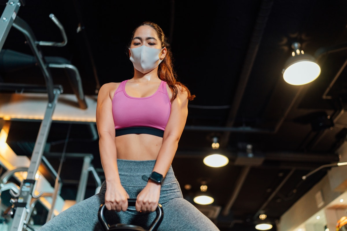 A person wearing a pink sports bra and a mask performs a kettlebell deadlift in the gym. Lifting weights can help you live longer.