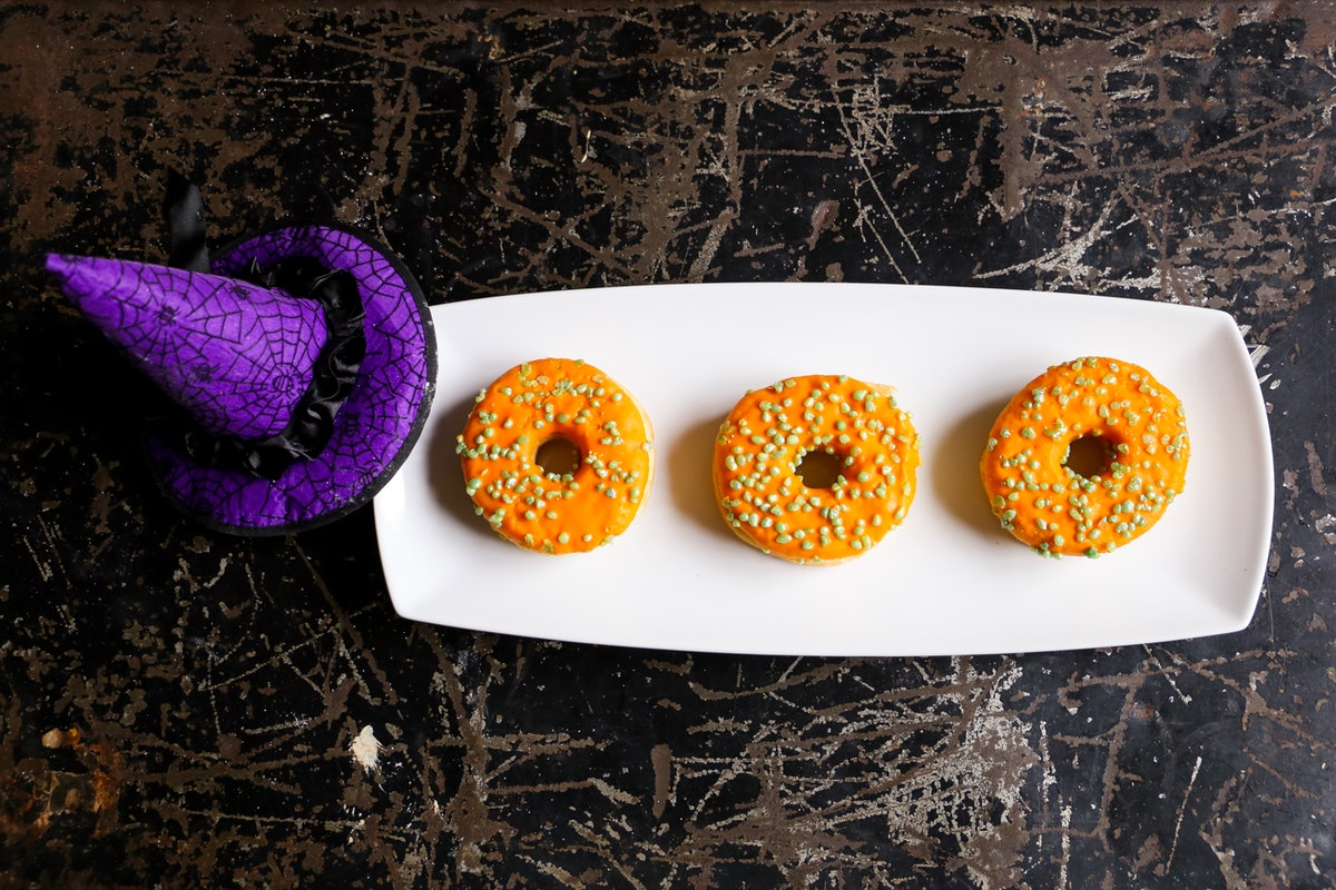 A plate with three Halloween orange doughnuts sits on the counter next to a purple witch's hat.