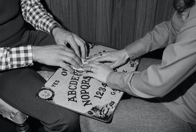 Vintage photo of people using a ouija board. The history of the ouija board demon Zozo is internet lore.