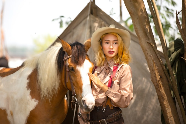 A young Asian woman stands next to a horse while wearing a cowgirl hat, pink suspenders, and pastel blouse.
