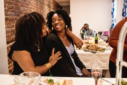 two women hugging at thanksgiving, hostess