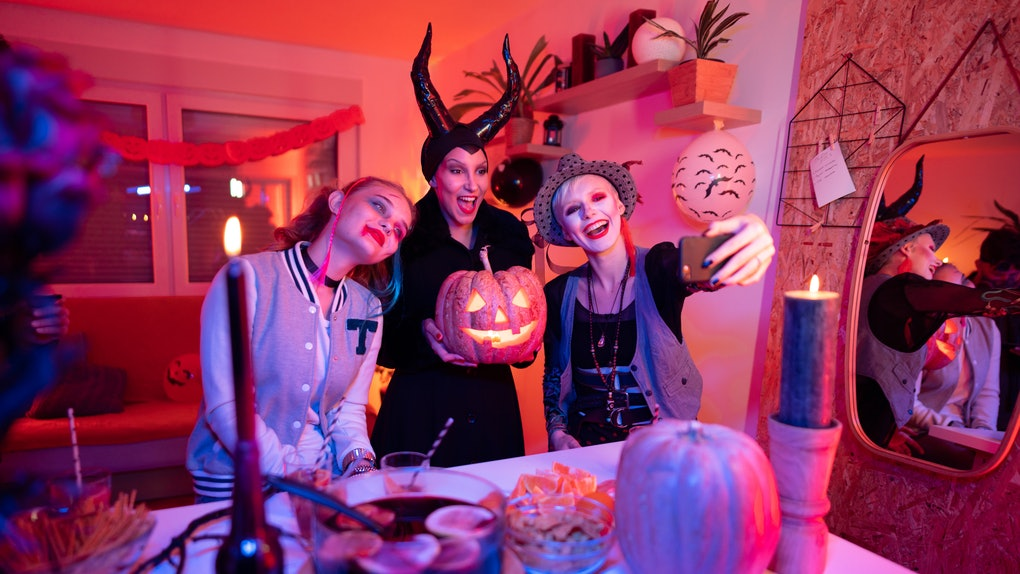 Three friends dressed in Halloween costumes pose for a phone selfie with their jack-o-lantern at home in front of a festive punchbowl.