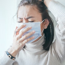 A person wearing a mask covers her nose with one hand. There are some key differences between coronavirus and allergies.