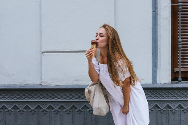 A young woman wearing a white dresses kisses a chocolate ice cream cone on the street.
