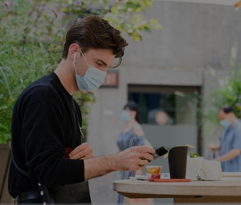 Man wearing AirPods and a face mask.