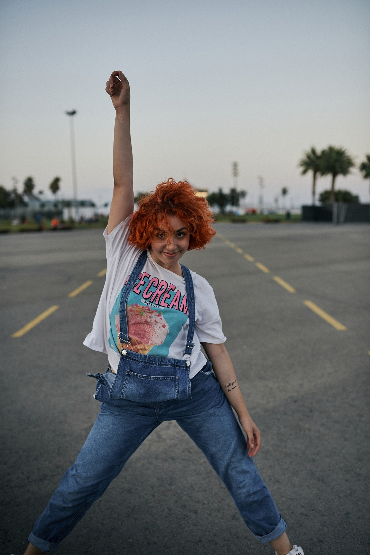 A young Latinx woman with orange hair and spunky style poses in a parking lot with palm trees at dus...