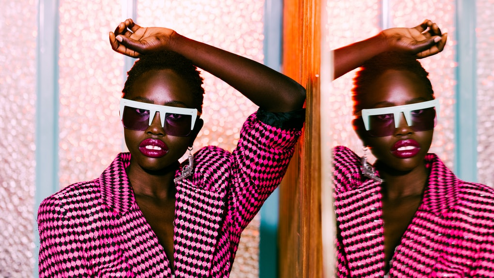 A young, fashionable Black woman poses in a black and pink blazer against a mirror for a fashion magazine.