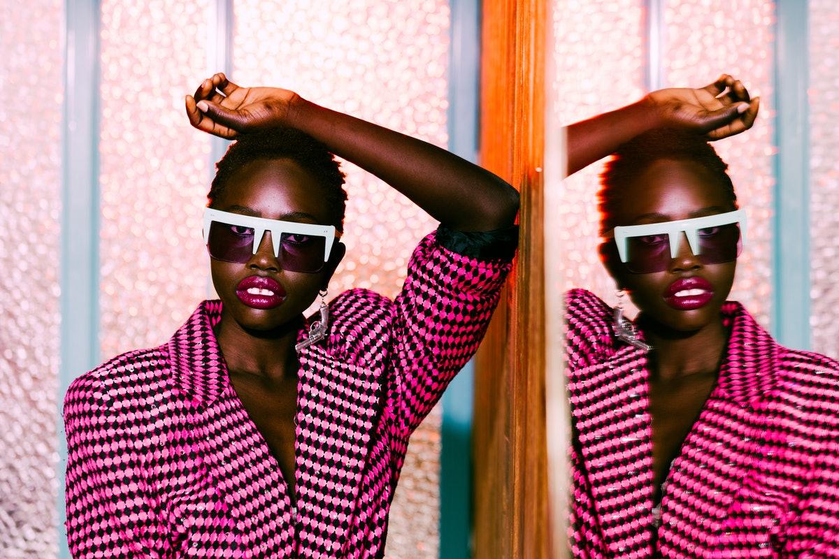 A young, fashionable Black woman poses in a black and pink blazer against a mirror for a fashion mag...
