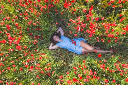 A woman dreaming in a field of flowers. Déjà rêvé is the experience of feeling like you've dreamed something before.