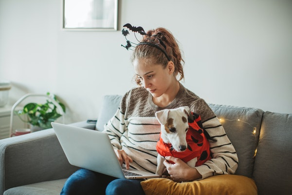 A young woman sits with her dog and her laptop on a couch, while wearing a headband with bats on her head.
