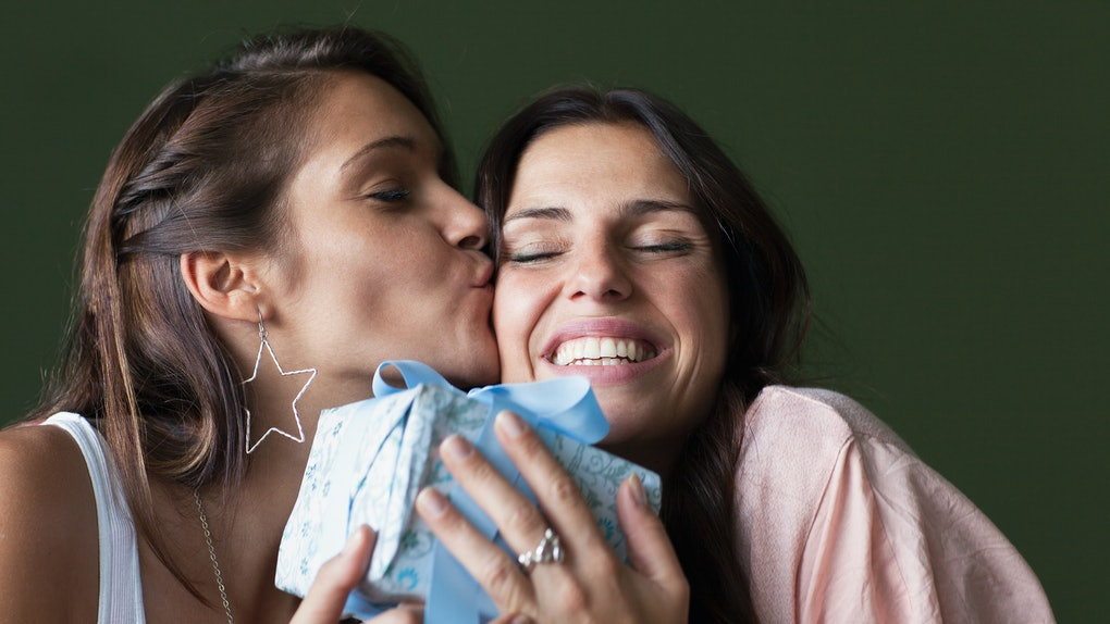 A woman gives her best friend a wrapped gift and kiss on her cheek.