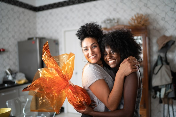 Two friends hug in their kitchen, while one holds an orange wrapped gift.