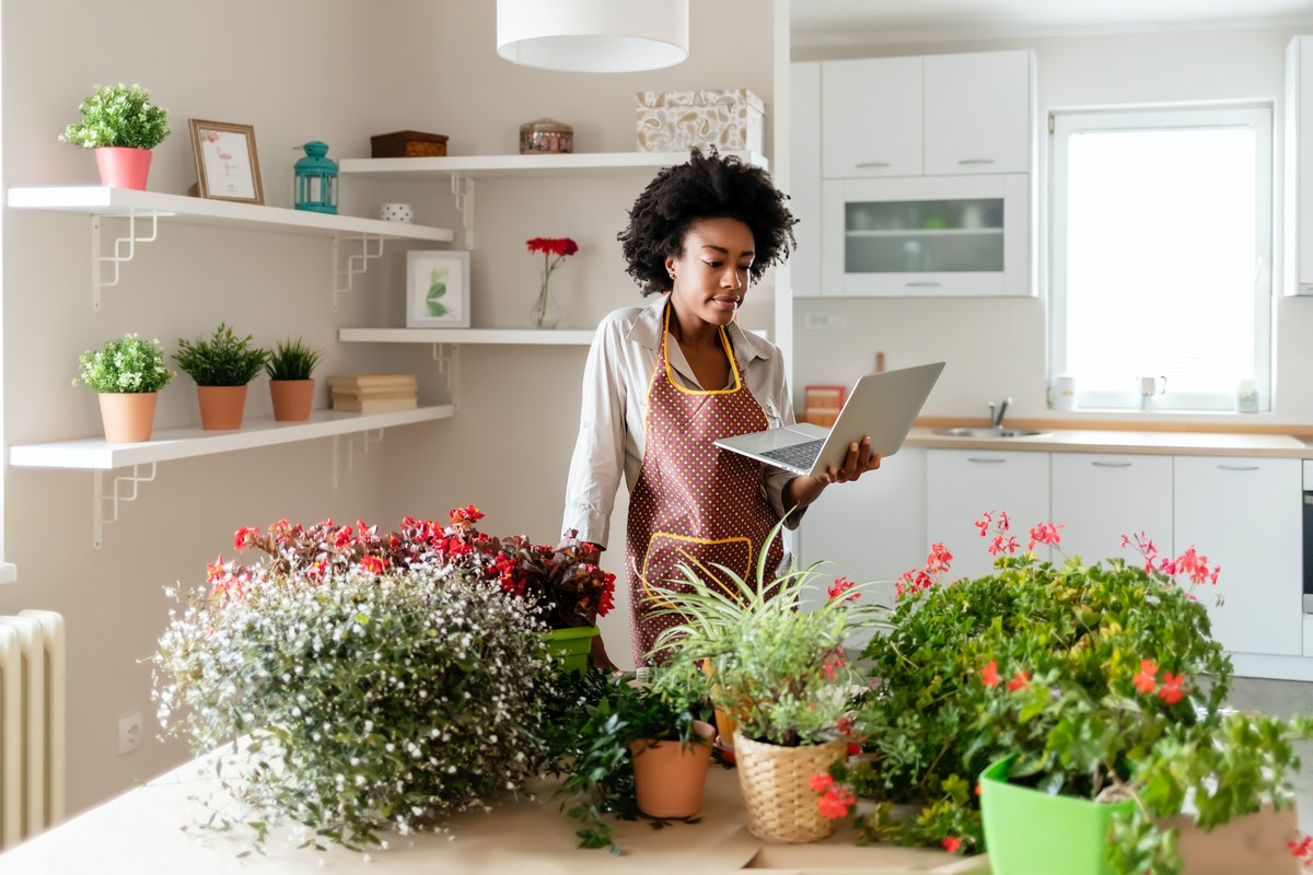 A young Black woman looks at her laptop while standing next to a table filled with potted plants in ...