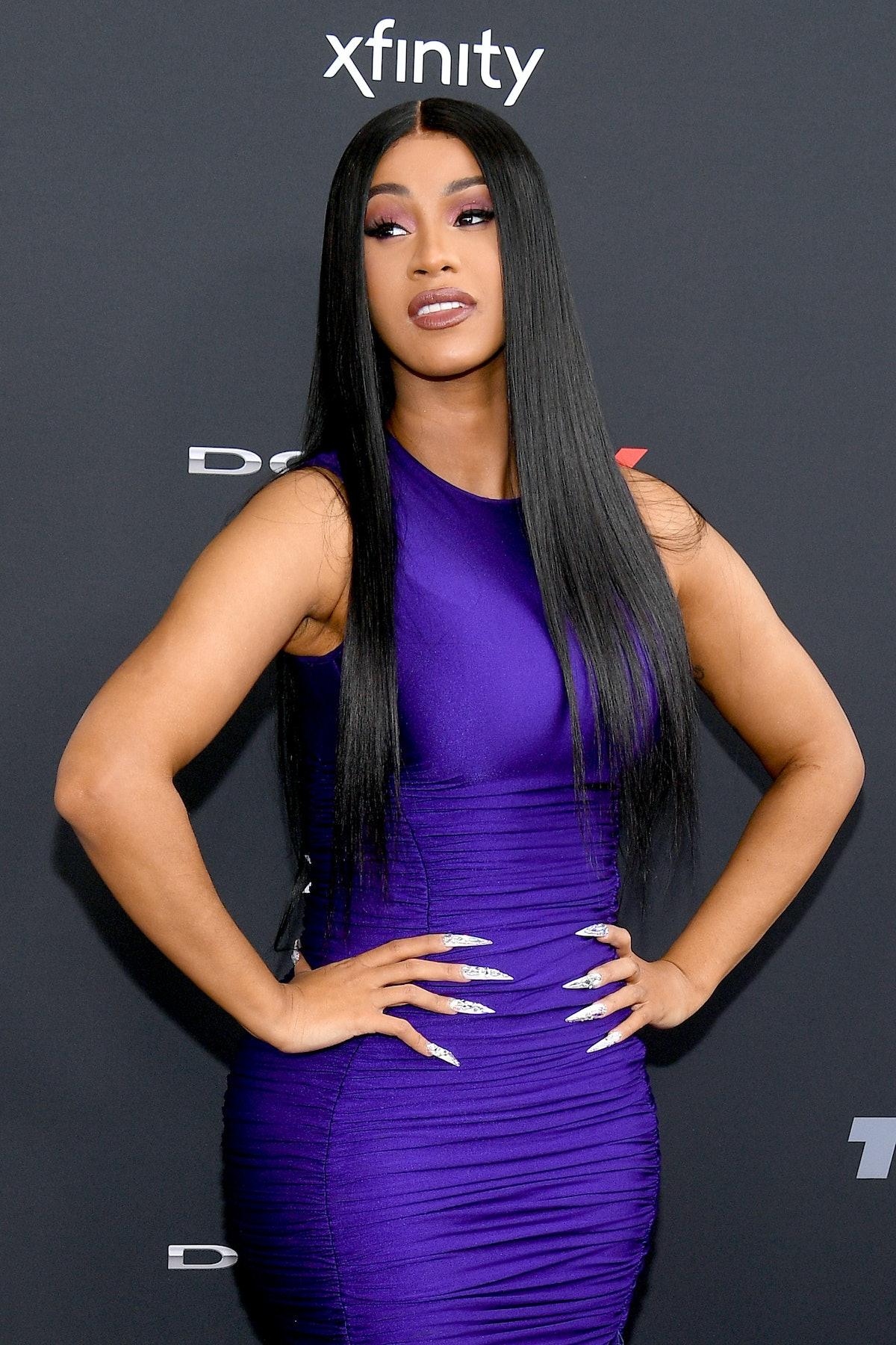 Cardi B hits the red carpet in a purple dress.