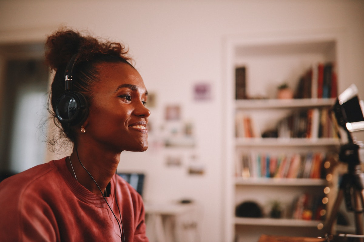 A young Black woman sits at her laptop while wearing a pink crewneck and headphones.