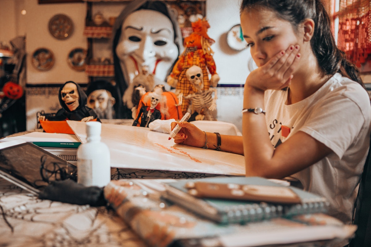 A young woman draws with an orange marker while sitting near Halloween decorations.