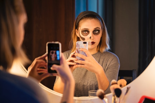 A young woman wearing Halloween makeup poses in her bathroom mirror for a selfie.