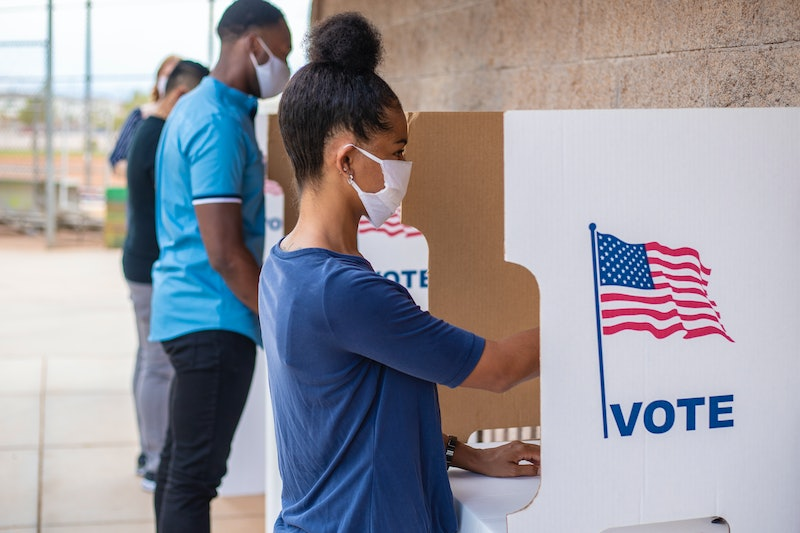 Young woman voting with a mask