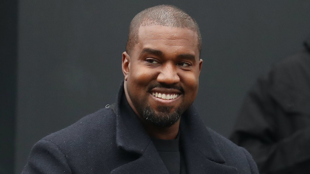 Kanye West flashes a smile.