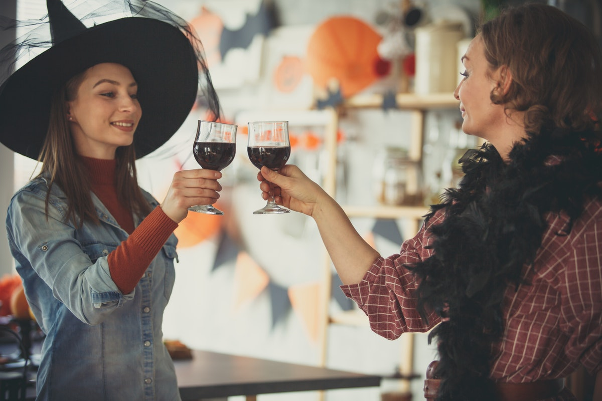 Two women dressed up for Halloween cheers with their wine glasses in the kitchen.