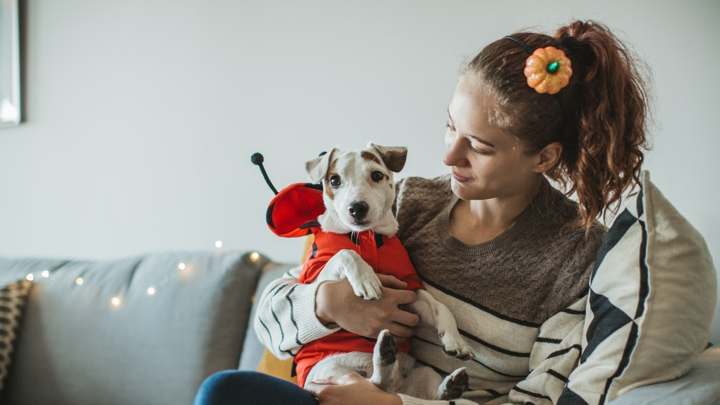 A young woman sits with her dog on the couch while they're both wearing Halloween costumes.