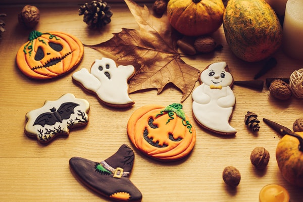 Beautifully-decorated Halloween cookies are placed on a kitchen counter next to pumpkins and Halloween decor.