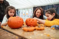 mom and girls carving jack-o-lanterns