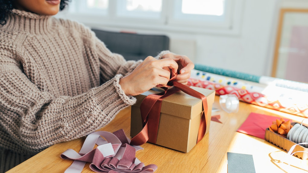 A young Black woman wraps up a present in her home with purple and rust ribbon while wearing a chunky turtleneck.