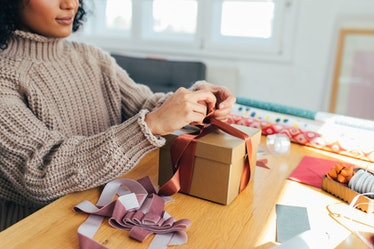 A young Black woman wraps up a present in her home with purple and rust ribbon while wearing a chunk...