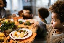 little girl eating at thanksgiving table