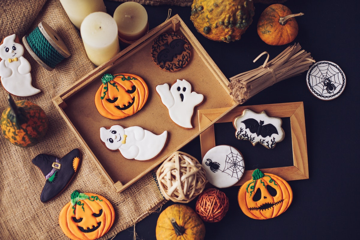 A batch of Halloween cookies, decorated like pumpkins, spiderwebs, and witch's hats, are place on th...