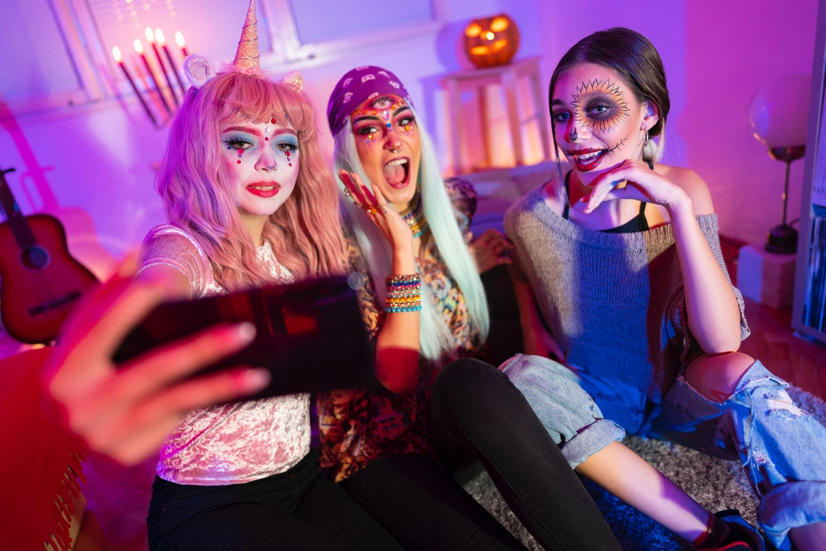 Three friends dressed up for Halloween record a video on their phone.