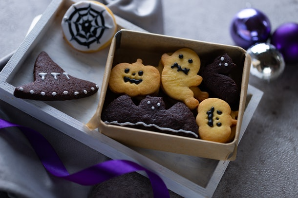 Some Halloween cookies made to look like ghosts and bats sit in a box on the table.