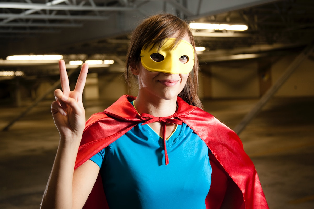 A woman wearing a superhero costume gives a peace sign, while standing in a garage.