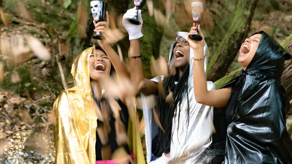 Three women raise Halloween cocktails in the air while dressed up in costumes in the woods.