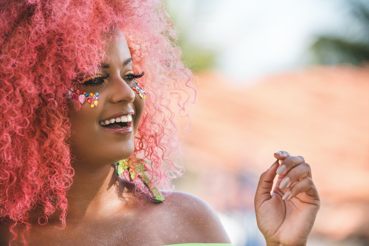 A woman wearing a glitter makeup look with rhinestones on her face is outside.
