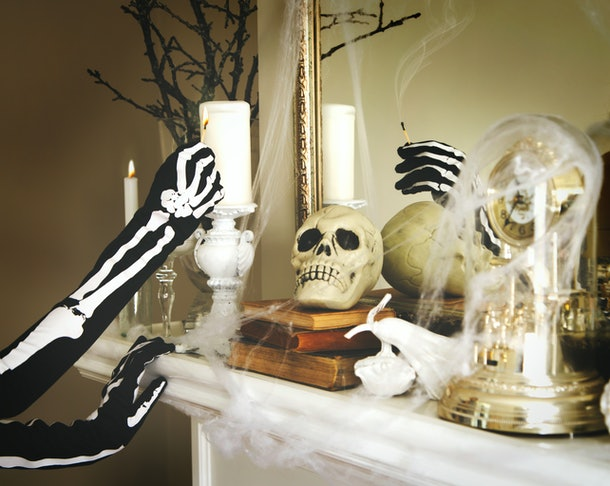 A young woman wearing a skeleton costume lights a candle on a fireplace with Halloween decor.