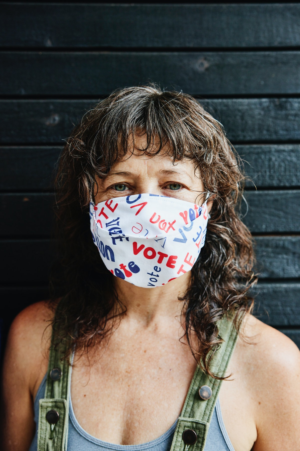 A woman wears a voting face mask. Voters responded to a Bustle and Mic survey on voting and covid op...