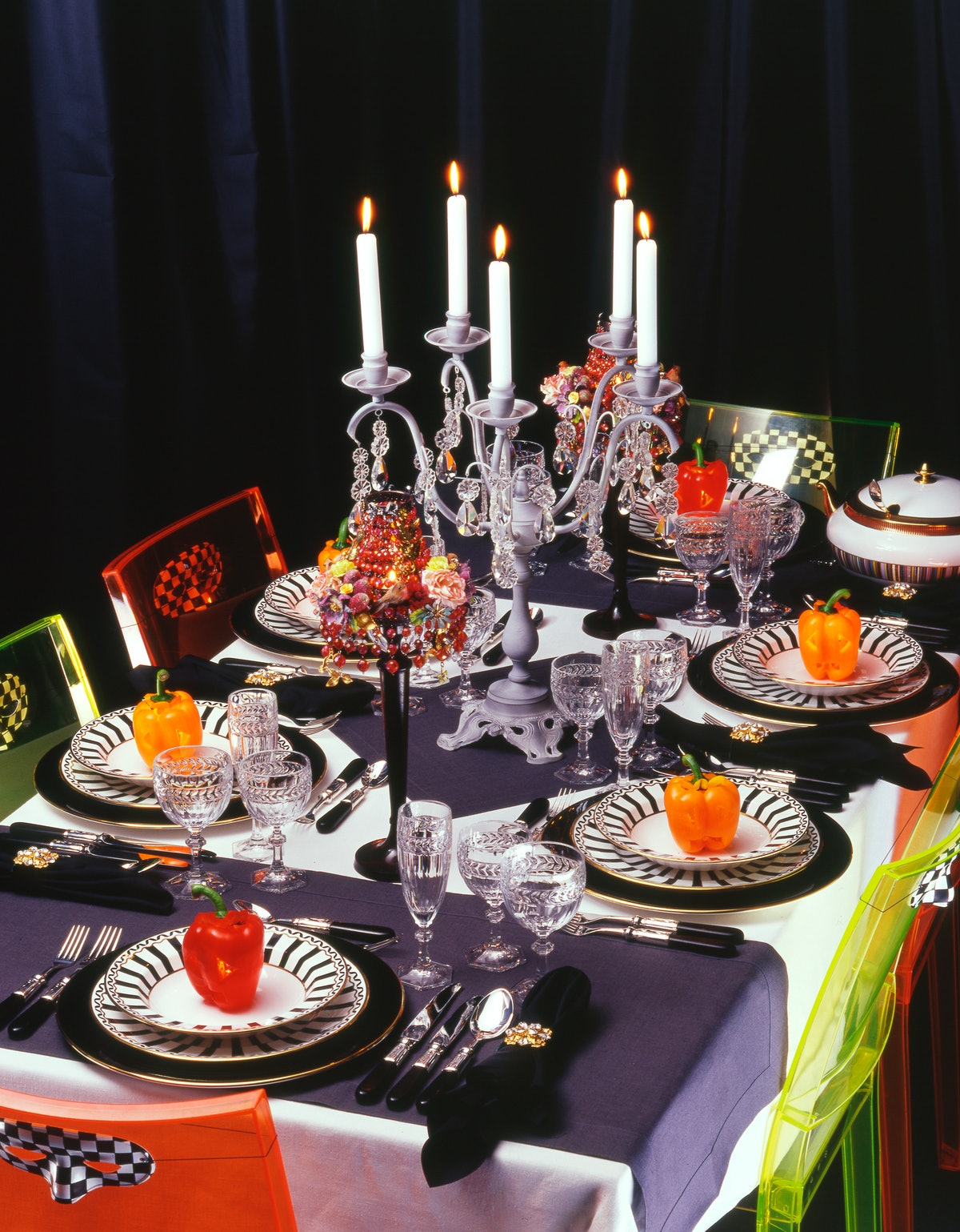 A Halloween dinner table is set with black napkins, black and white plates, candles, and face masks ...