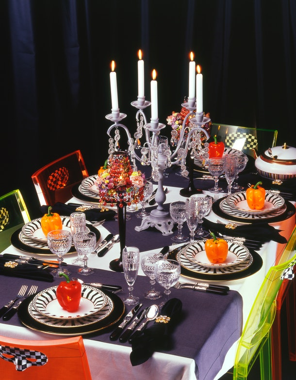 A Halloween dinner table is set with black napkins, black and white plates, candles, and face masks on the chairs.