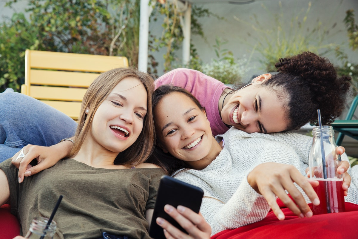 Three happy friends huddle together outside with soda, while looking at something on their phone.