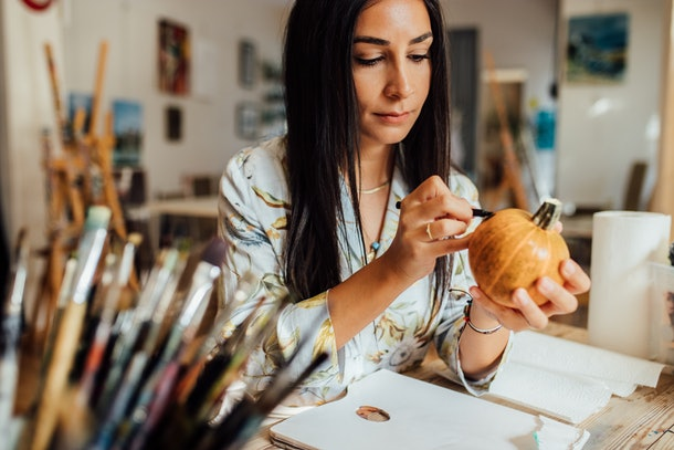 A young woman draws on a pumpkin while sitting at a table in her home.