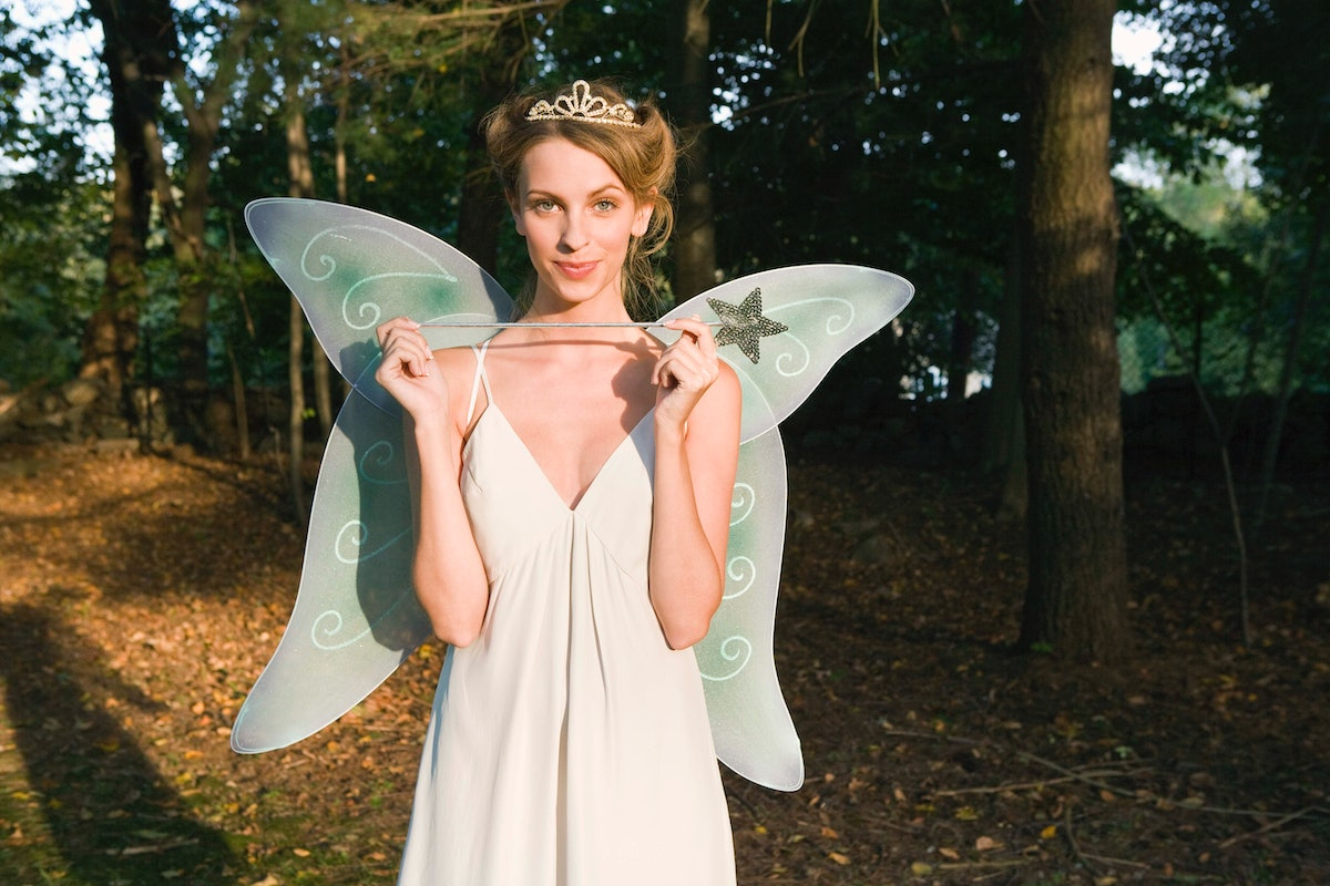 A woman dressed like the Blue Fairy from 'Pinocchio' stands in the woods with her wand and wings.