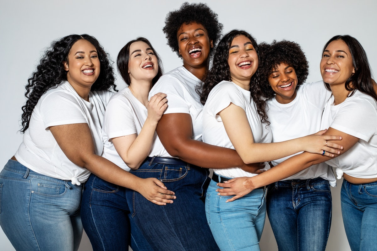 A group of woman all wearing white t-shirts and blue jeans huddle up.