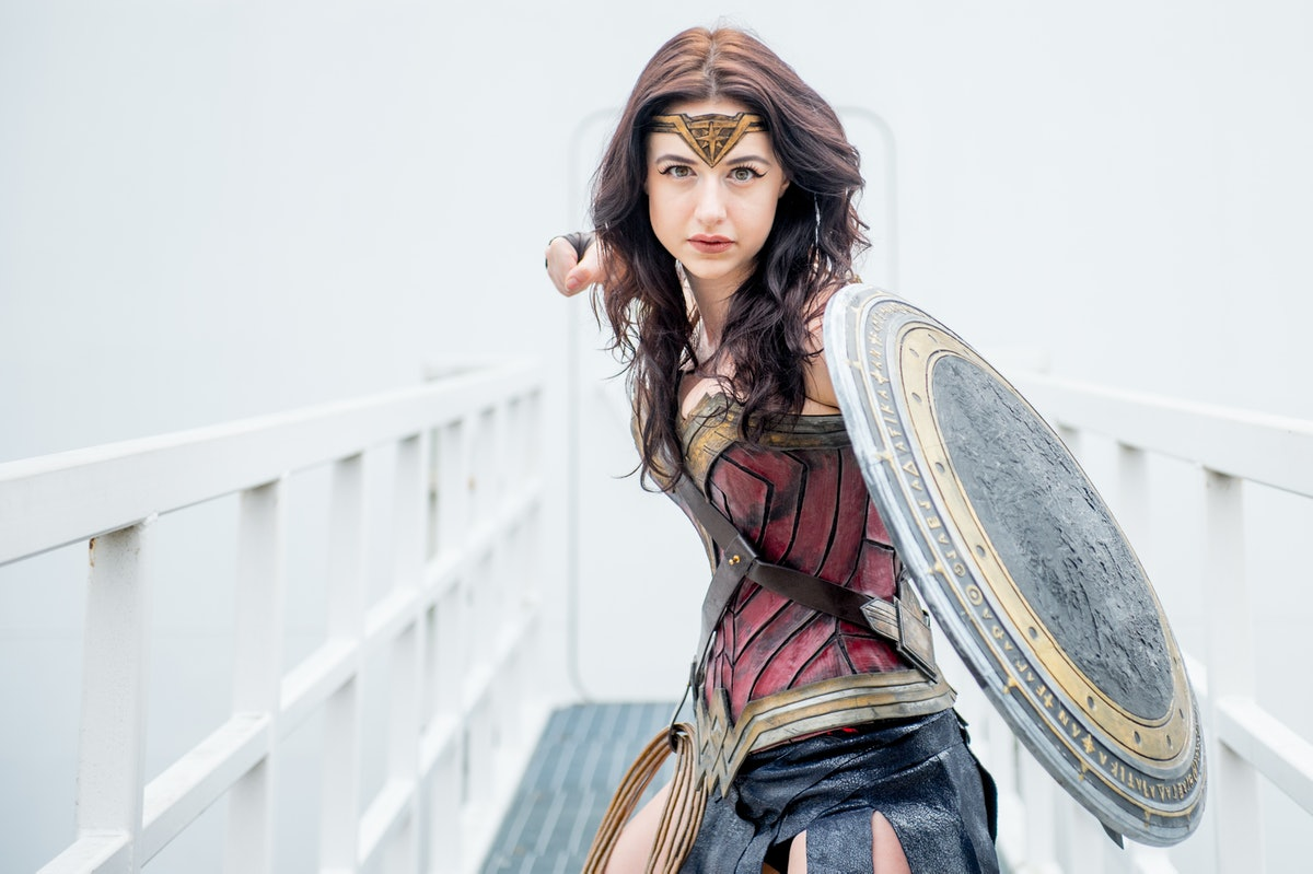 A woman dressed like Wonder Woman for Halloween lifts her fist in the air.