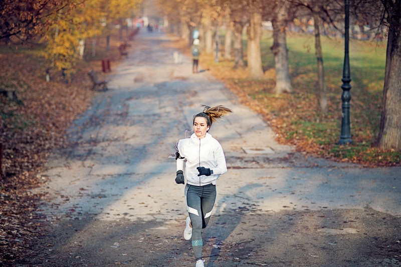 A woman runs on an autumn road listening to a political podcast.