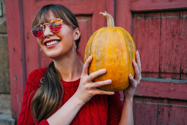 A young woman holds a pumpkin while standing against a red barn and wearing red-tinted sunglasses.